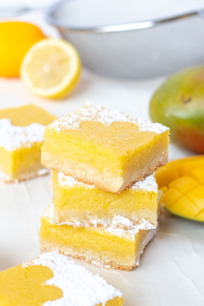 Tart Lemon Mango Bars // Perfectly tart and sweet mango bars with a shortbread cookie crust are the perfect way to celebrate the summer and bring for parties and potluck snacks! Make with fresh mango puree and lemon juice, they're sweet with the perfect amount of bite #mango #fruitbars #shortbread #summertreat #summerrecipes #summerdessert