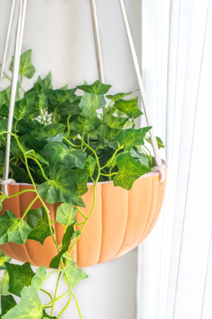 DIY Hanging Pumpkin Planter for Fall // See how to cut a fake pumpkin to make a hanging planter to decorate your home for fall! Fill it with your favorite faux plants or give one as a gift! #pumpkins #homedecor #falldecor #falldiy #halloweendiy #planter #plantlady #fakepumpkins #pumpkincarving