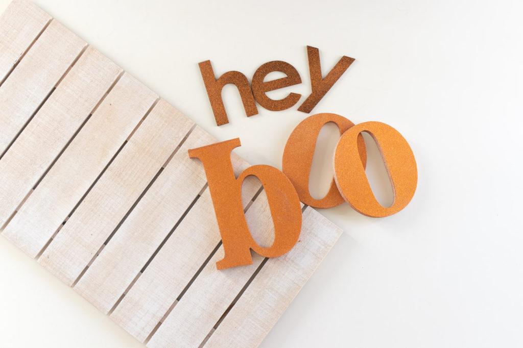 """Hey Boo"" Punny Halloween Sign DIY // Make a fun wooden Halloween sign with a punny saying to decorate your home for Halloween! Decorate your front door, fireplace or other corner of your home using supplies from @joann given a makeover with the NEW @rustoleum Imagine collection, including glitter spray paint #ad #handmadewithjoann #halloween #halloweendiy #homedecor #halloweendecor #painting #spraypaint"