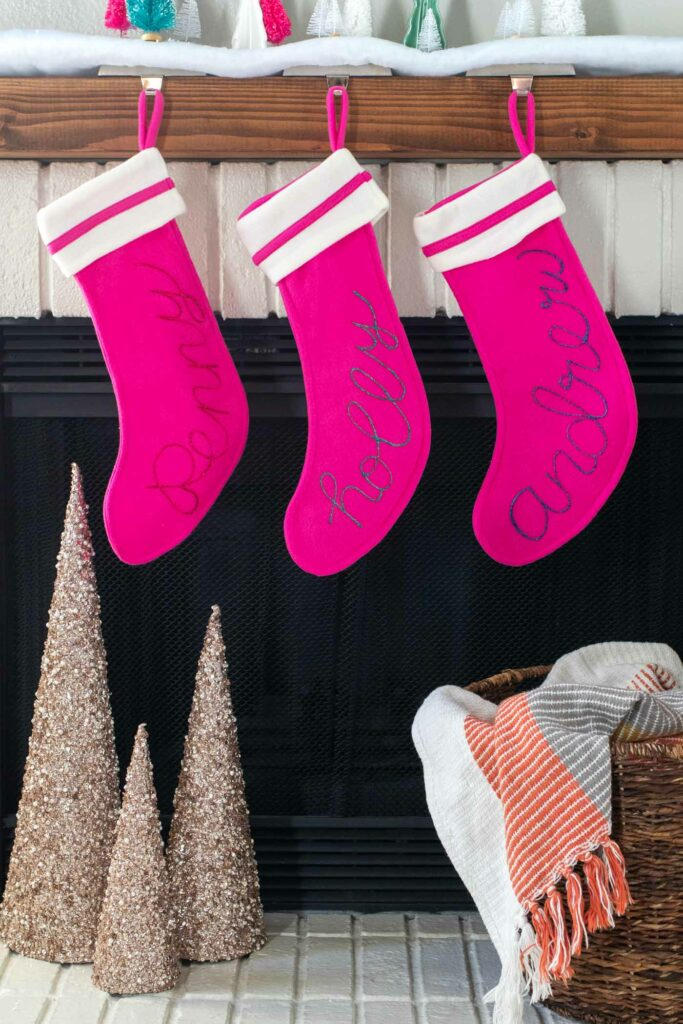 DIY Personalized Calligraphy Stockings // Decorate your mantel with new personalized stockings for the holidays! These DIY calligraphy stockings are easy to recreate with Tulip Dimensional Paints for everyone in your family this Christmas! #christmas #holidaydecor #stocking #stockingdiy #fabricpaint #painting #calligraphy #handlettering