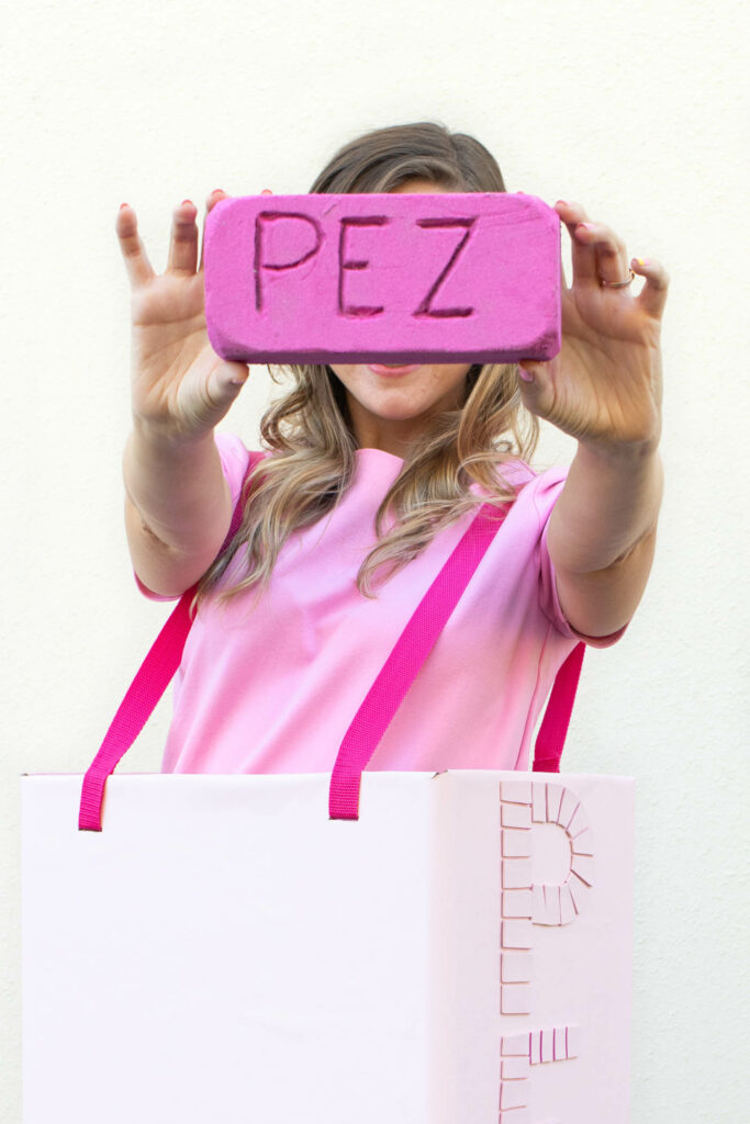 DIY PEZ Container Costume for Halloween // Repurpose a cardboard box into a PEZ container Halloween costume for kids or adults! Plus, make a PEZ candy out of foam! #diycostume #halloween #kidscostumes #adultcostumes #pezcontainer #90s #halloweendiy #halloweencostume