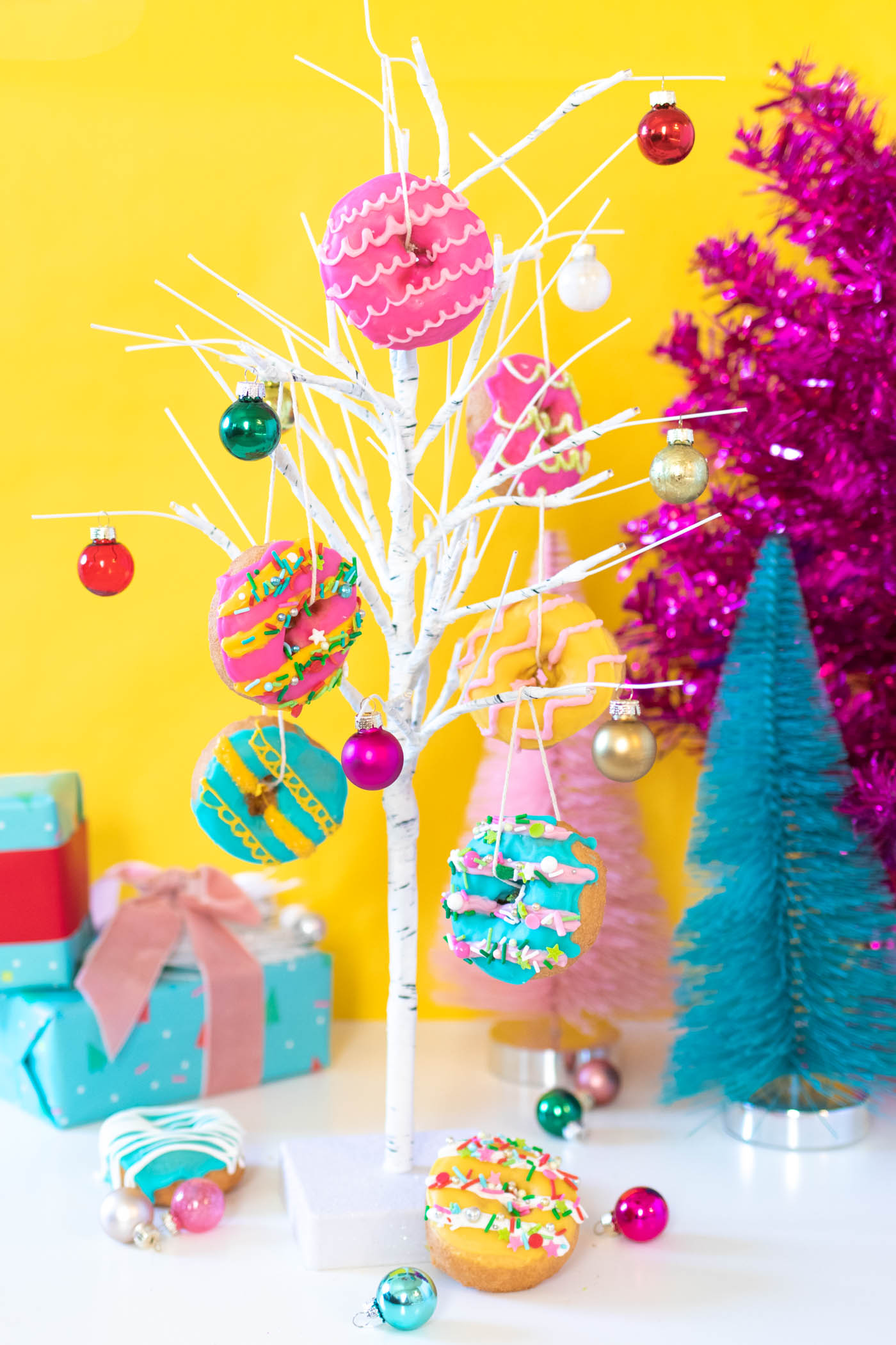 Edible Donut Ornaments // Decorate a Christmas tree or branches with these colorful edible donut ornaments! Display holiday donuts on a tree for a fun party treat or just for a fun weekend project #donuts #holidaydesserts #christmas #christmasfood #christmasparty #partyfood #donutdecorating #candymelts #christmasdecor #diychristmas
