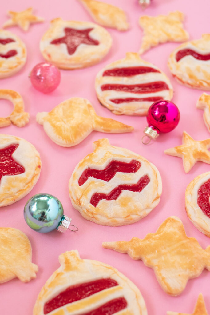 Ornament Pies // Christmas Hand Pies // Cut pie dough into ornament shapes with cut-out details for making cute mini Christmas pies! Fill with colorful cherry pie filling for a great holiday treat or after-dinner Christmas dessert #christmasrecipe #pie #handpies #christmasdessert #pierecipe #cookiecutters #diyornaments