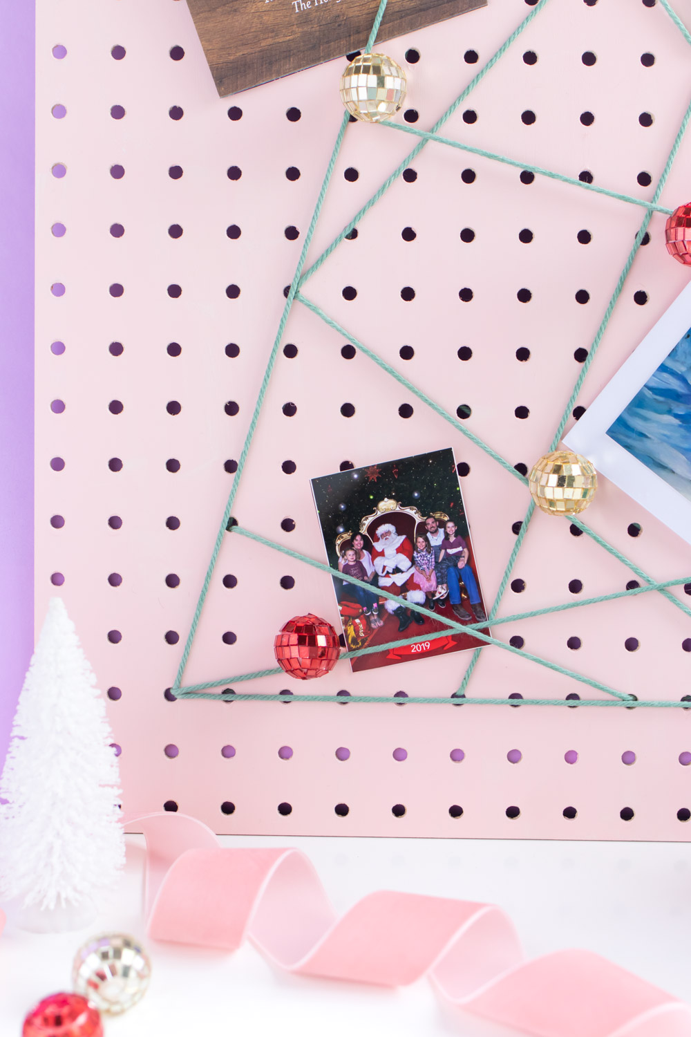 DIY Holiday Pegboard Card Holder // Turn a slab of pegboard into a fun Christmas tree card display inspired by string art! Display your holiday cards in a unique way with this DIY Christmas decor idea #christmasdiy #christmascard #christmasdecor #christmasstorage #pegboard #papercrafts #stringart #holidaystorage #cardstorage
