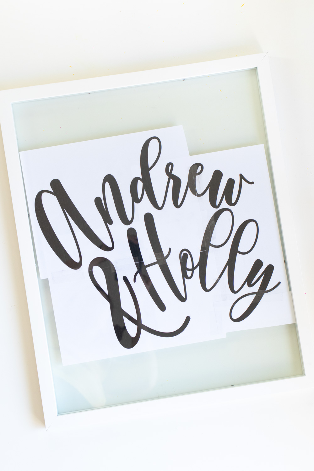 Easy DIY Calligraphy Wedding Sign // Use a large photo frame to make your own custom wedding signage with Rust-Oleum spray paints! Trace your names or sayings, then let it pop off the glass with the new Imagine collection of glitter spray paint available at @joann! #ad #handmadewithjoann #weddingdiy #diywedding #weddingsign #spraypainting #calligraphy #diyideas #homedecor