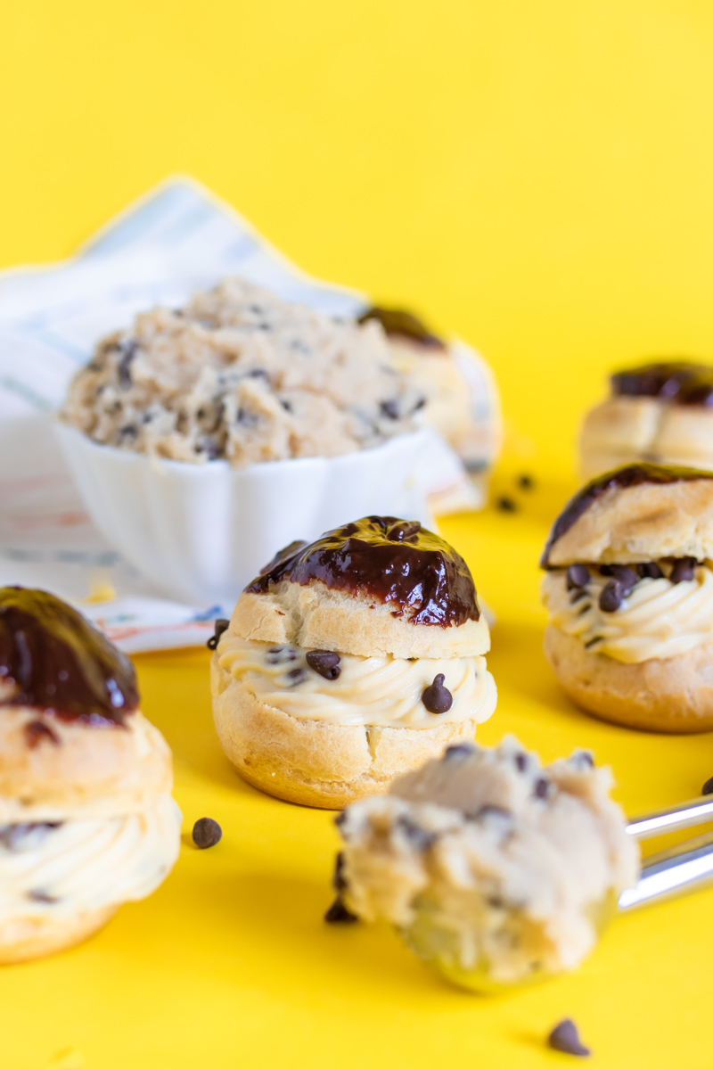 Cookie Dough Cream Puffs // Try this classic cream puff recipe with tips for making perfect pate a choux with a brown sugar pastry cream that tastes like cookie dough! These tasty edible cookie dough-like treats are perfect for parties #creampuffs #frenchpatisserie #frenchfood #dessertrecipes #cookiedough #cookierecipes #frenchbaking #pastries #pastryrecipes #partydesserts