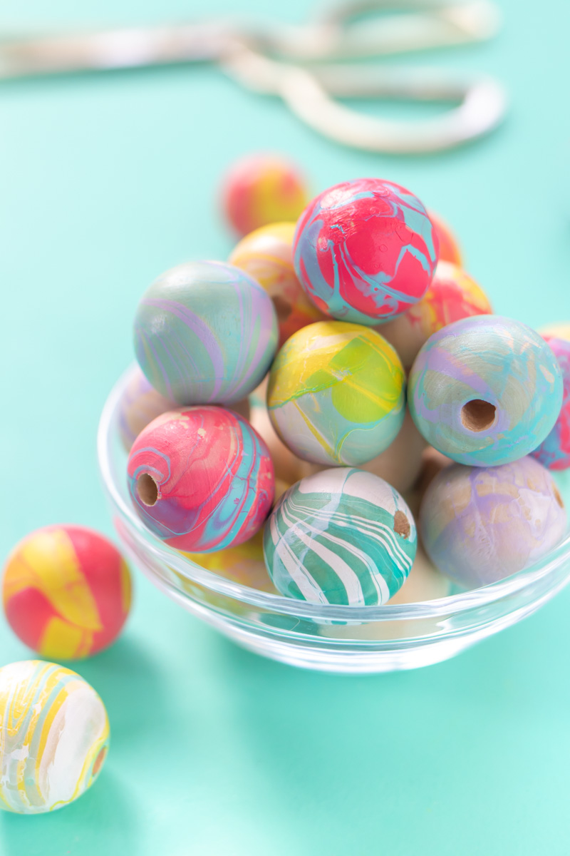 How to Nail Polish Marble Beads for Jewelry // Check out this guide to nail polish marbling with tips and tricks for creating marbled effects on almost any object! Make colorful marbled beads for jewelry, garlands and more! #budgetdiy #diyjewelry #marbled #nailpolish #nailart #painting #diyideas #diysforteens