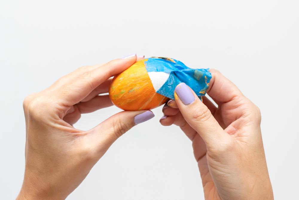 peeling tape off of fluid painted egg