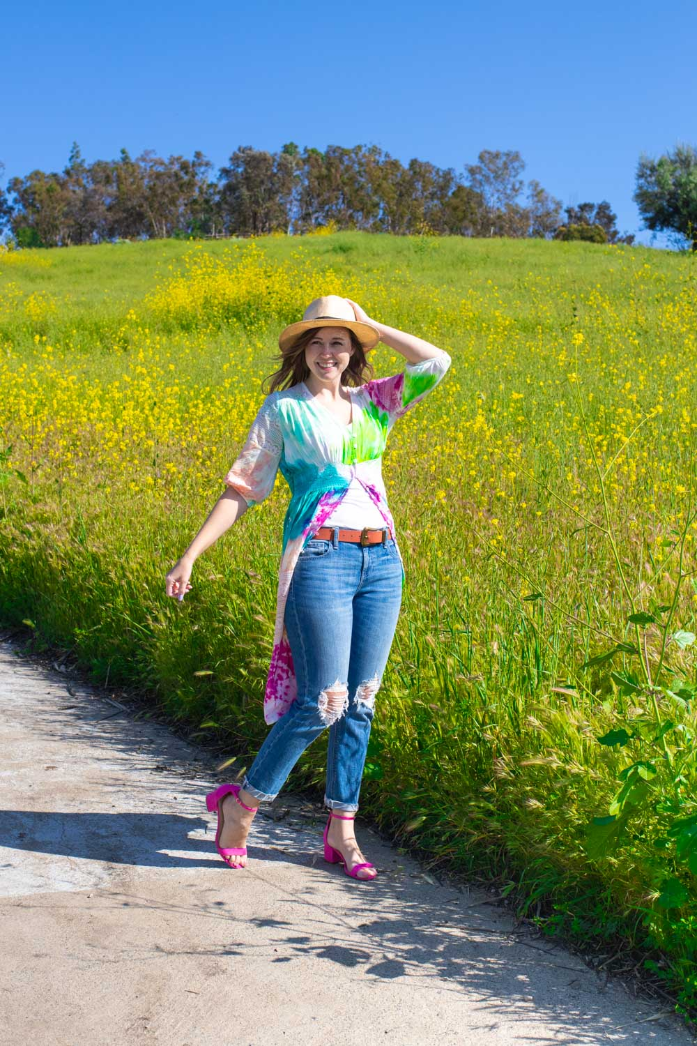 woman wearing tie dye kimono with jeans in front of wildflowers