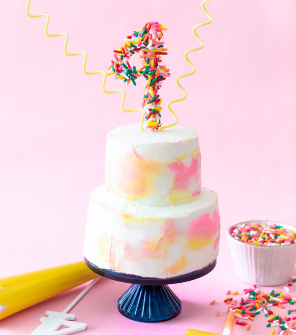 miniature cake with sprinkle number topper on pink
