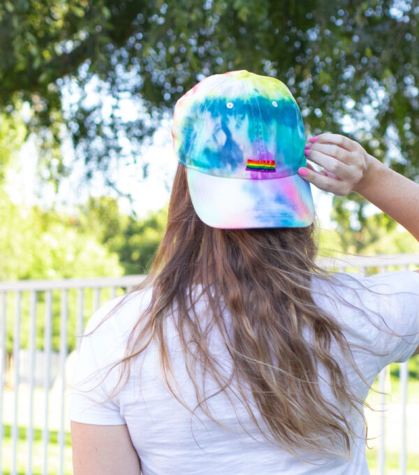 girl wearing backwards tie dye hat with painted pride flag