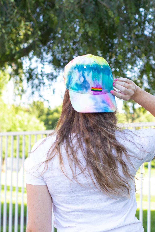 girl wearing backwards tie dye hat with painted pride flag