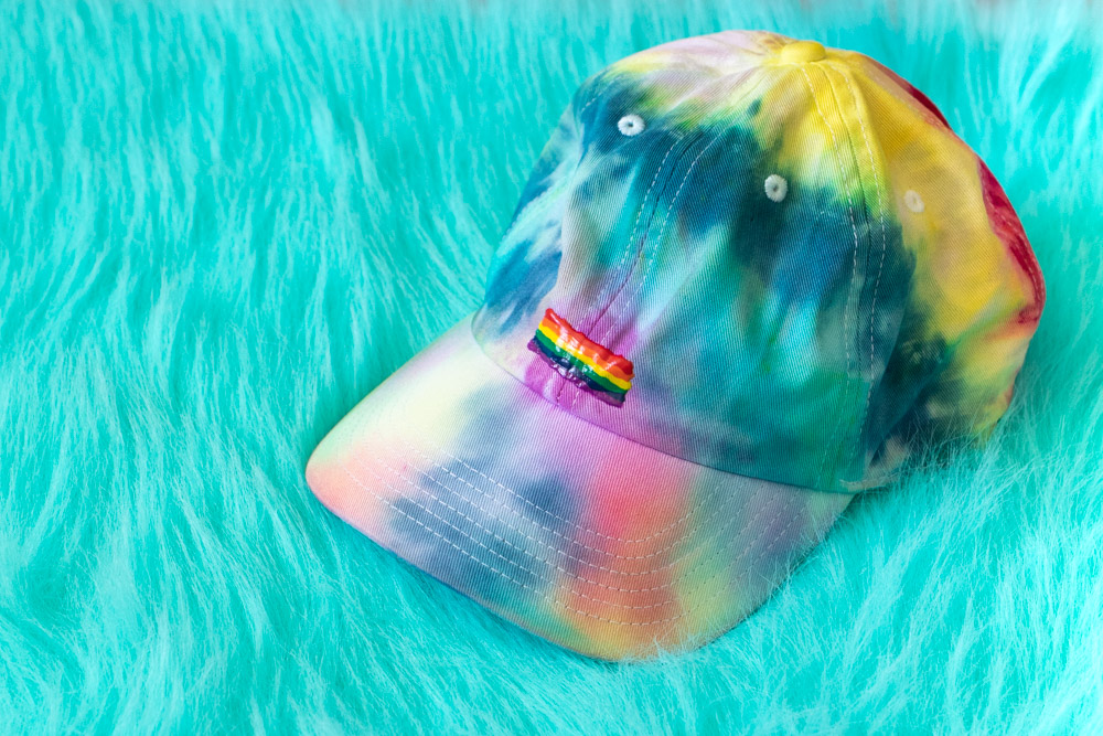 tie dye hat with pride flag on blue shag