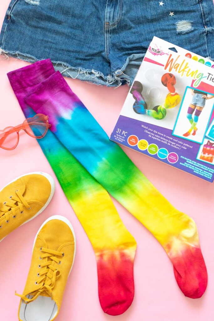 flatlay of thigh high socks with rainbow pattern and accessories