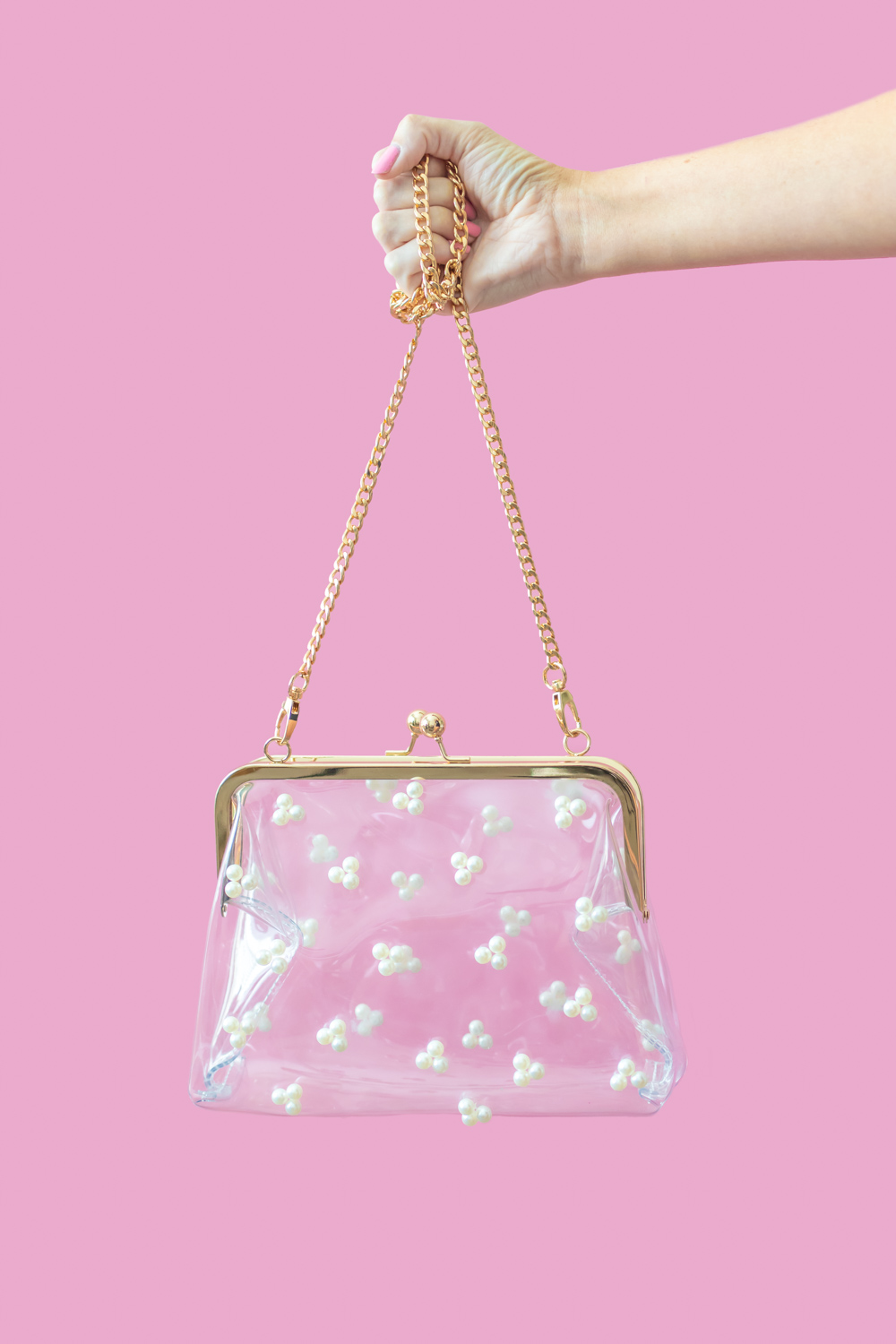 hand holding a clear pearl purse