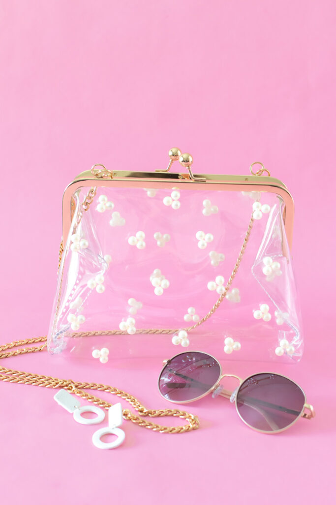 clear pearl stadium bag next to sunglasses and earrings