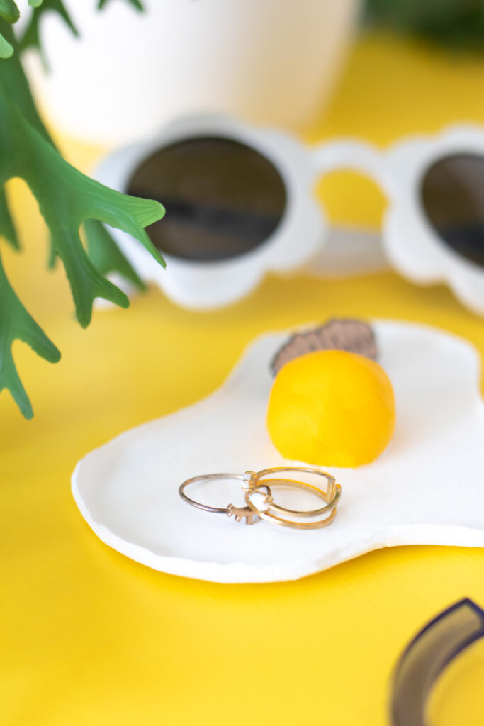 side view of fried egg clay trinket dish with rings and sunglasses