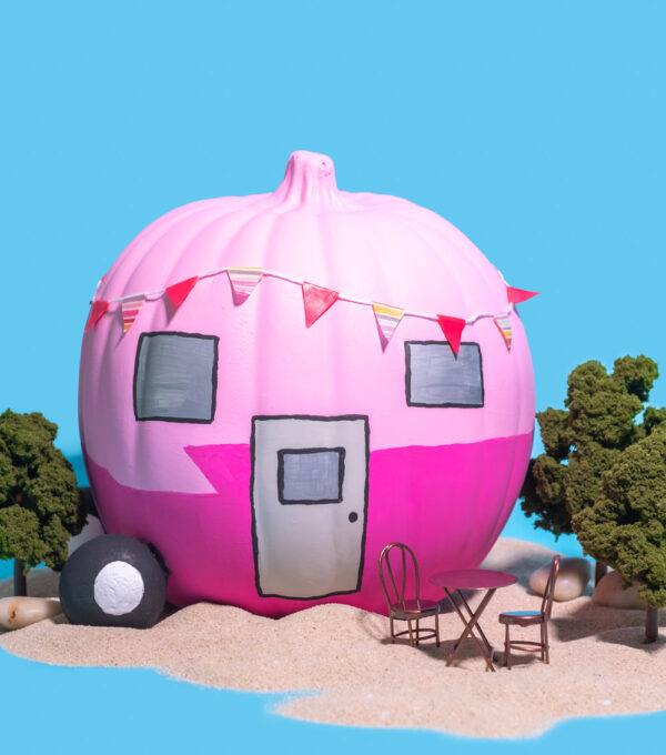 colorful vintage trailer pumpkin on blue background with sand and trees