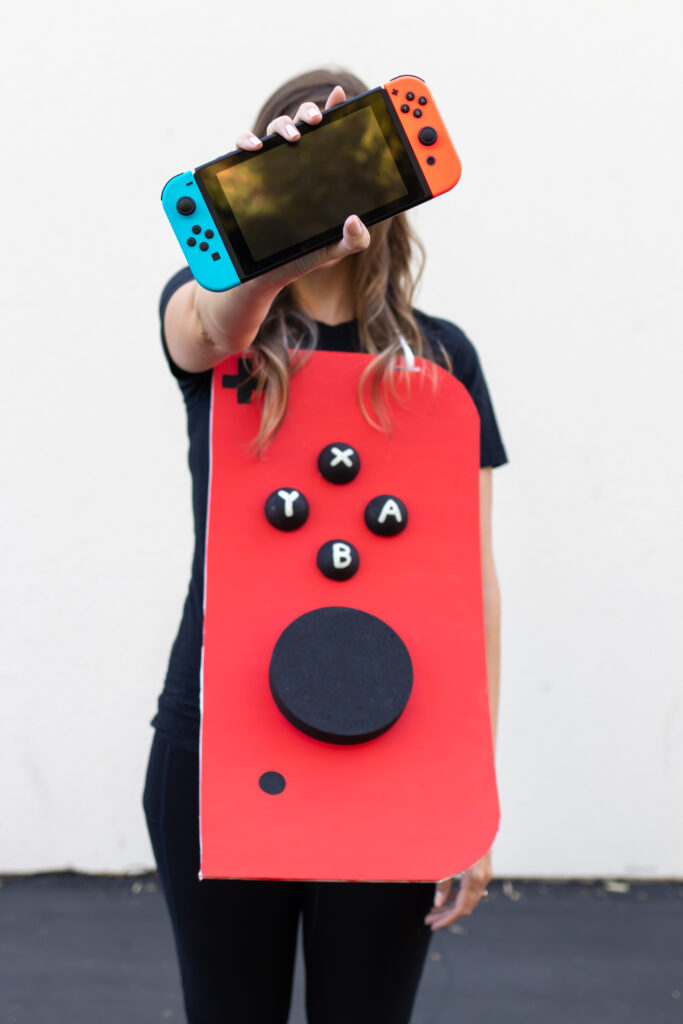 woman in video game couples costume holding Nintendo Switch