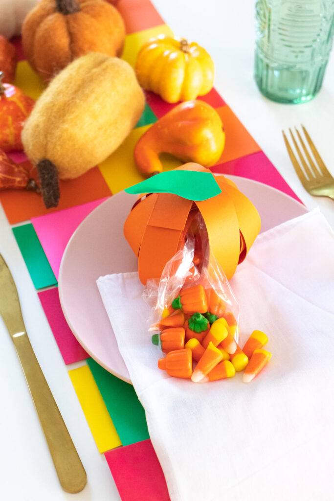candy spilling out of pumpkin treat bag made of paper
