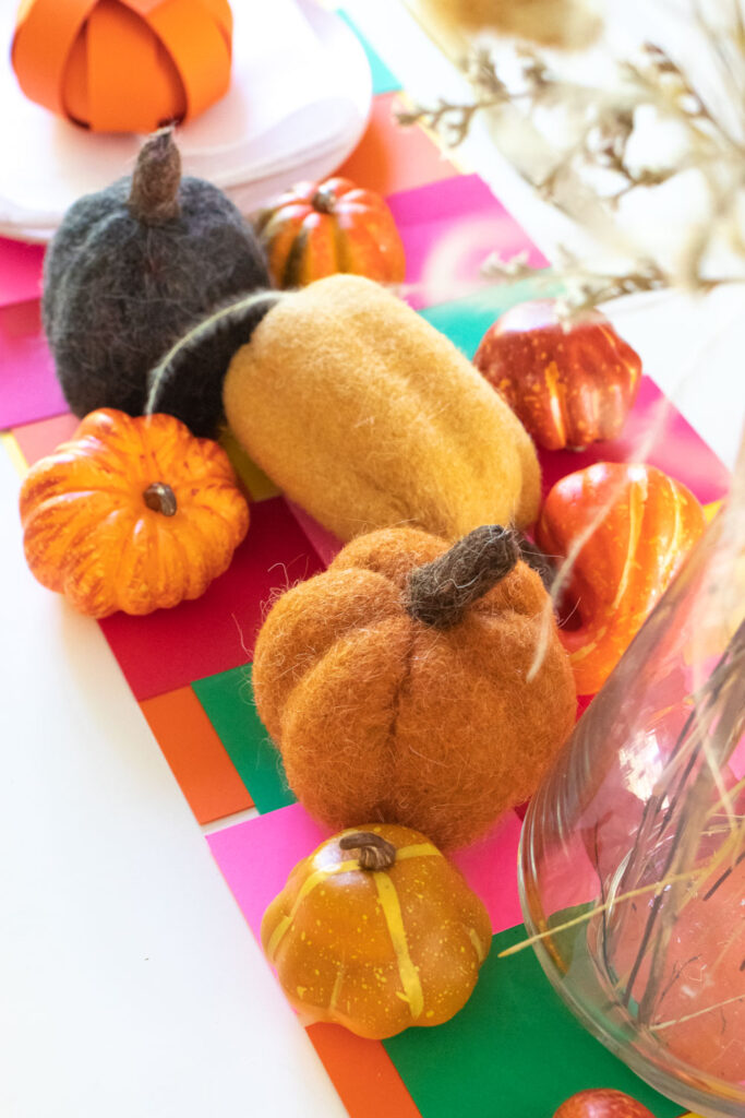 closeup of woven paper placemat and mini pumpkin decor