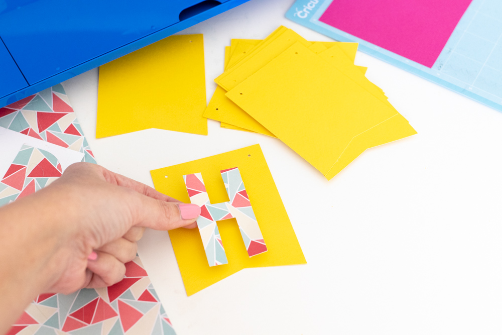adding sticker letters to colorful bunting
