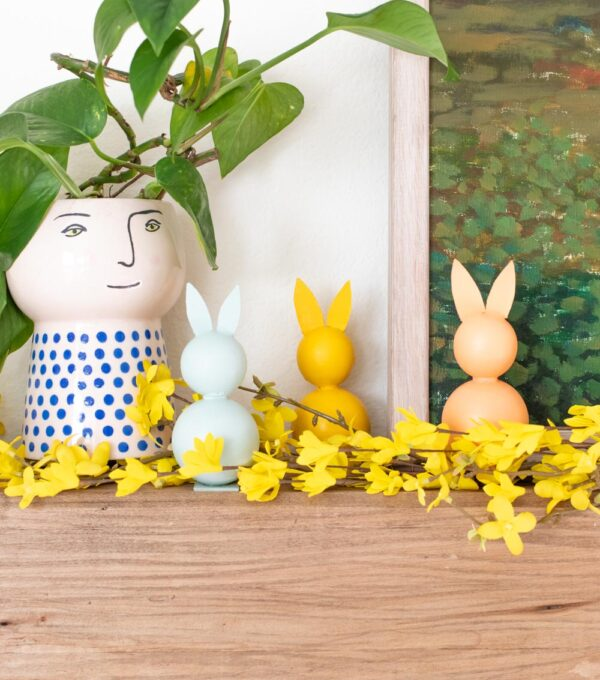 three modern easter decor bunnies on a mantel with a plant