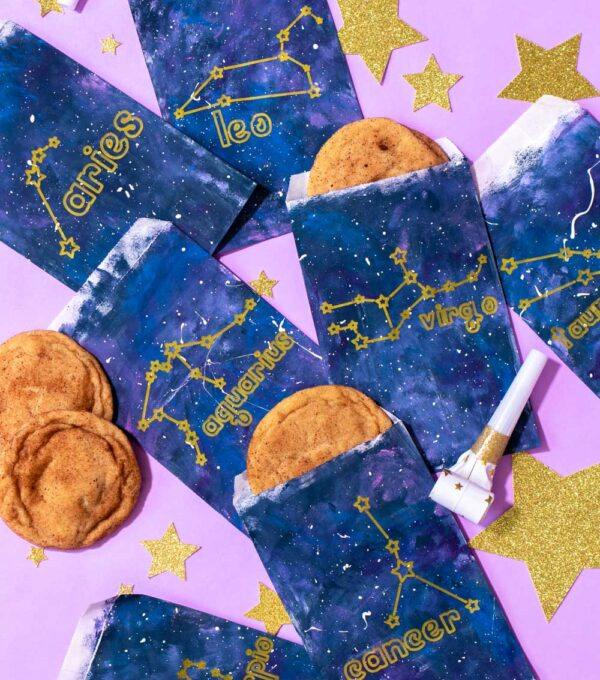 collection of zodiac-themed treat bags with cookies and glitter stars