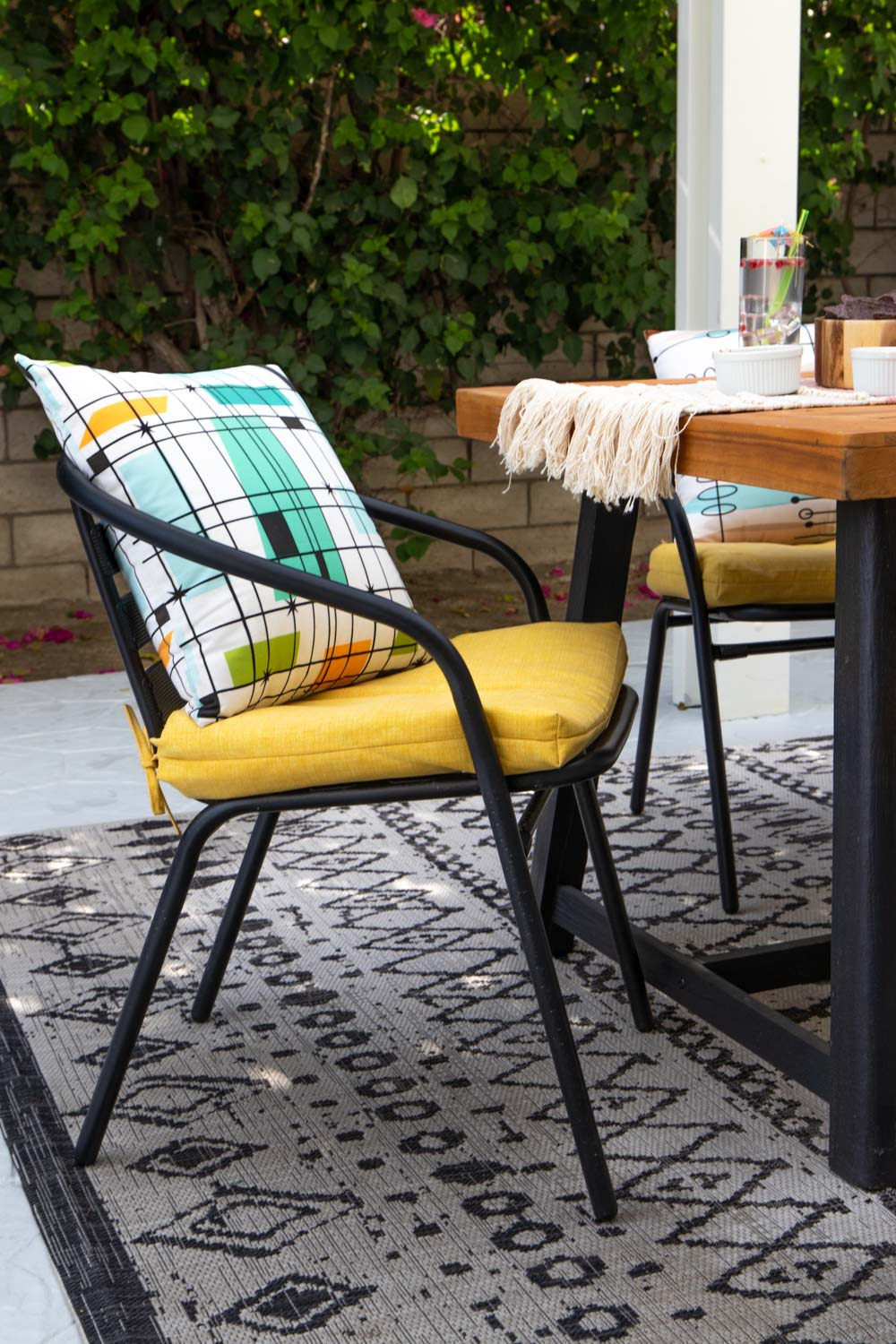 black outdoor chairs with yellow cushions