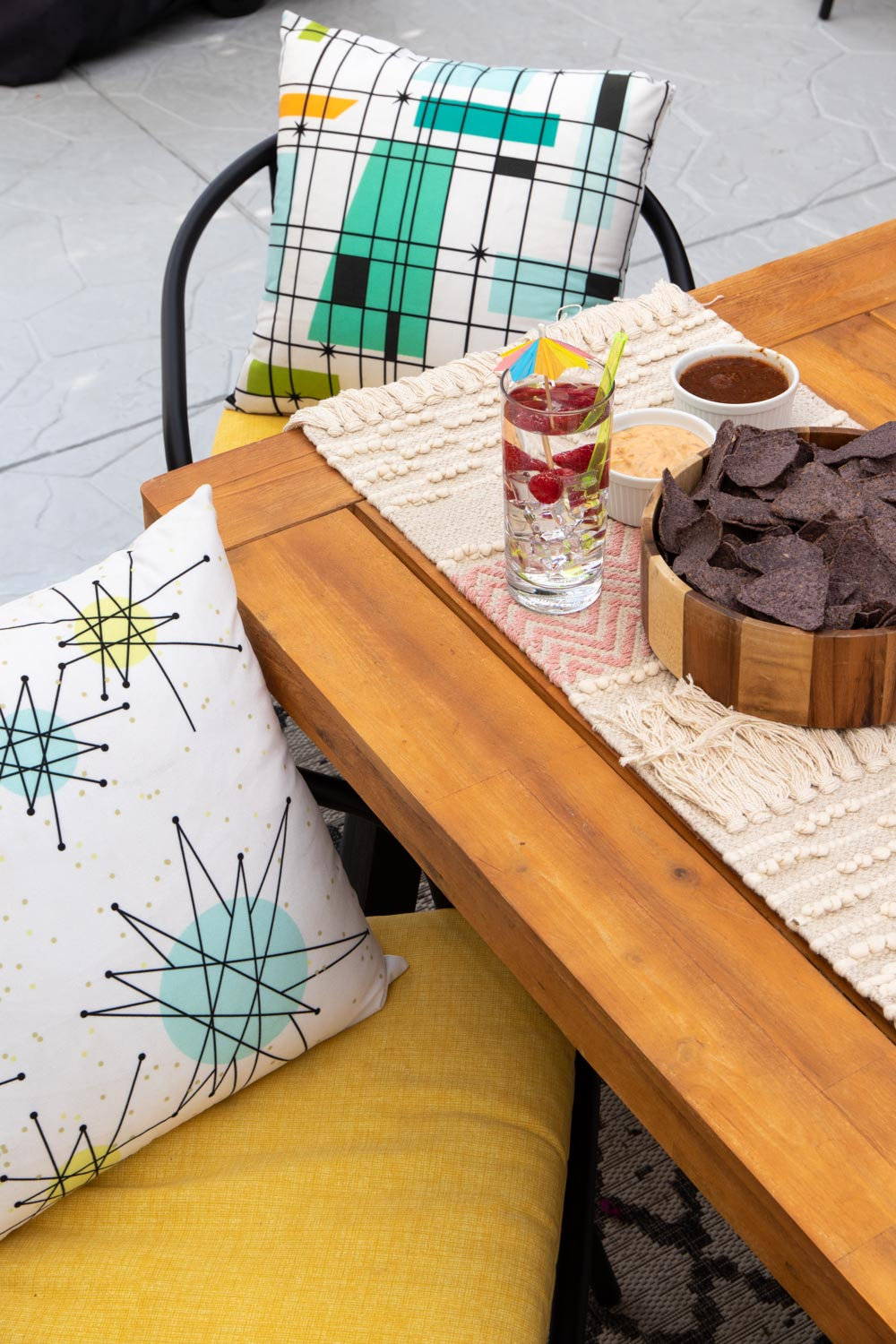 outdoor table with accessories and yellow cushions
