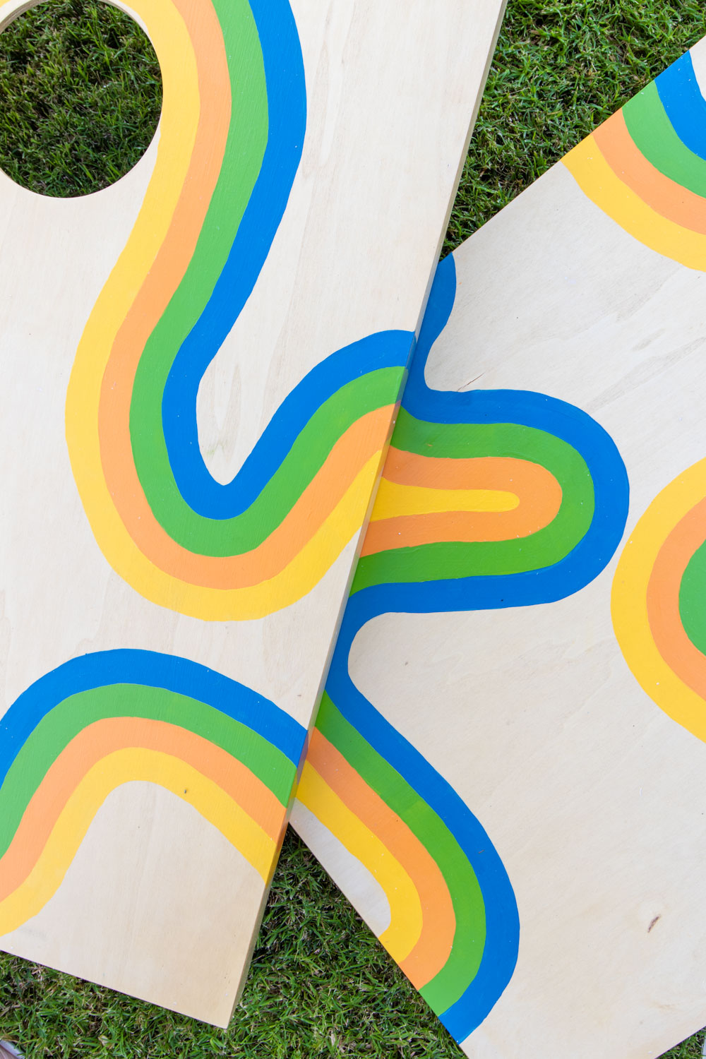 closeup of 70s-inspired painted cornhole makeover