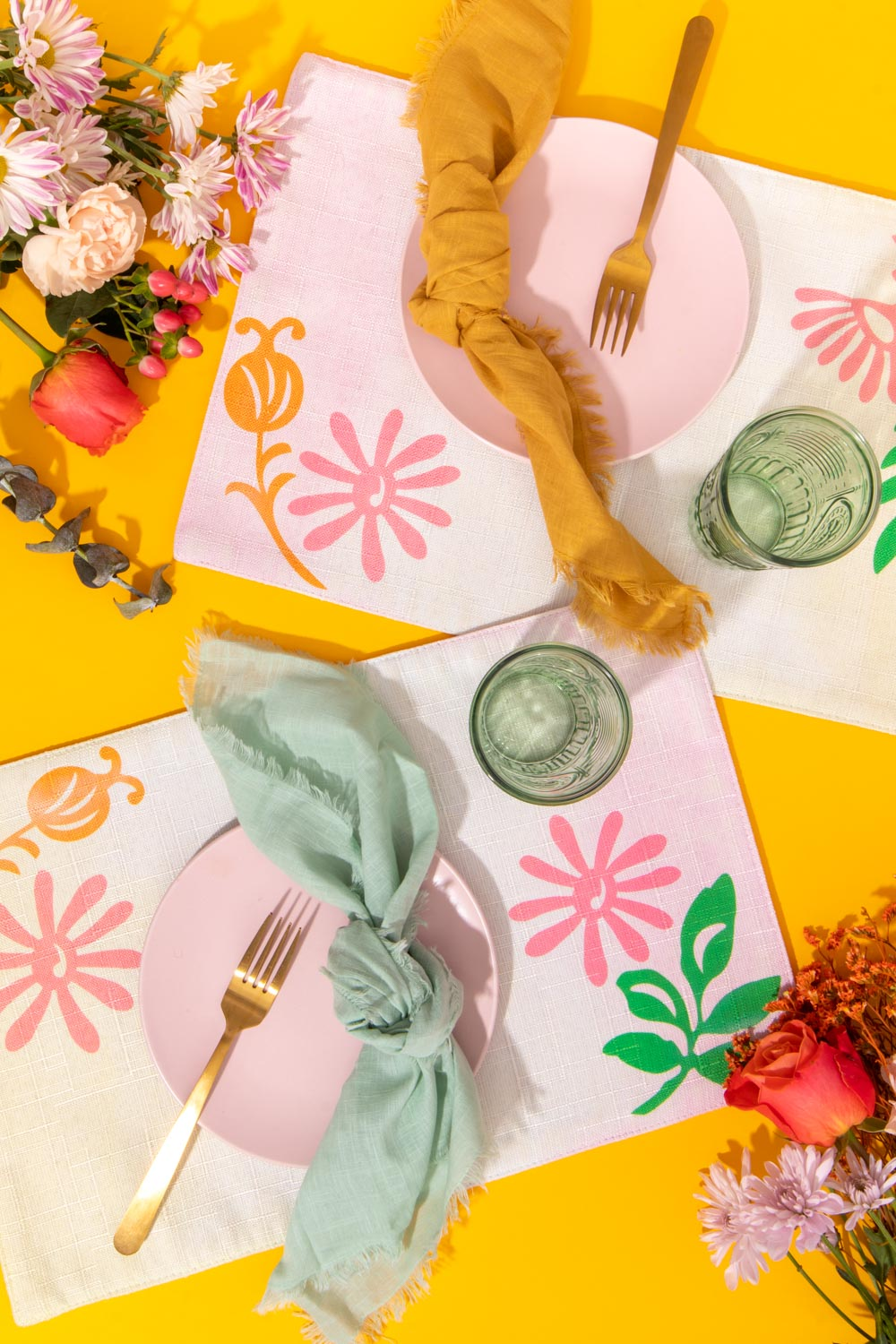 overhead view of two modern floral placemats with place settings and flowers