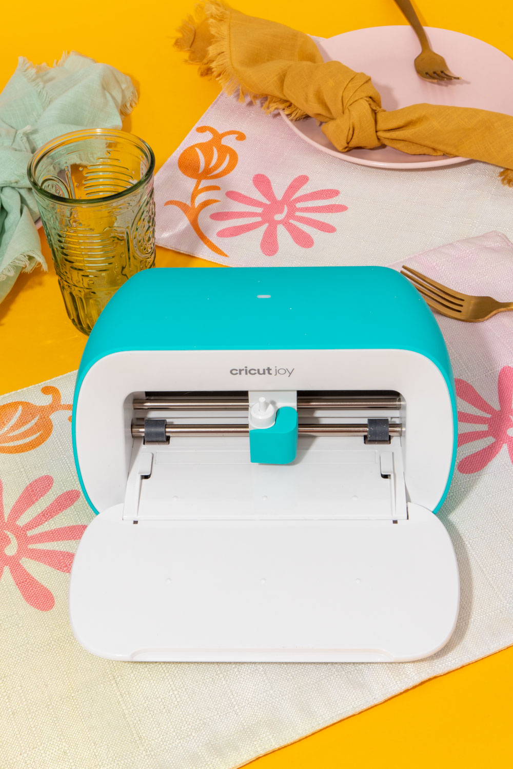 Cricut Joy on top of floral placemat on yellow background